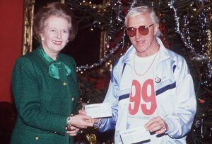 ©ALPHA 050000 1989 MARGARET THATCHER. - PRESENTING A CHEQUE TO THE TV CELEBRITY JIMMY SAVILE LONDON.